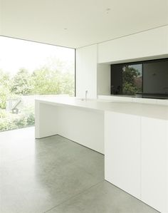 White kitchen with concrete floor and minimal window frames. House DZ in Mullem by Graux & Baeyens Architecten.