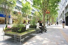 """Shoppers stop to rest on green benches centered around a """"satoyama"""" unit in Tokyo's Marunouchi district (Photo by 5 x Midori)"""