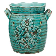 A traditional vessel in trendy blue-green is embossed with ornamental flowers, distressed and antiqued, imparting the look of a cherished vintage object.