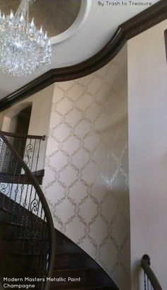 A gorgeous staircase accent wall stenciled with Modern Masters Champagne Metallic Paint | By Trash to Treasure