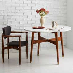 Set in stone. With its solid marble top and pecan-stained solid wood base, the Reeve Dining Table's round, compact size works for a breakfast nook or smaller dinner party. Brass-capped feet give it a finished feel.