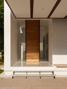 Sleek wooden door - Mandai Courtyard House by Atelier M A