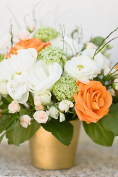Orange and white flowers in gold vase