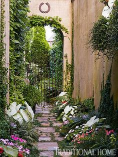 A narrow sandstone path, densely lined with ferns, hostas, and impatiens, leads to a backyard loggia and garden.