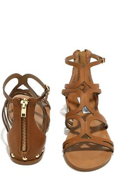 "Complete your Boho-chic ensemble with the Steve Madden Delta Tan Leather Gladiator Sandals! Slender genuine leather straps cross over a peep-toe upper to form these trendy gladiator sandals, with adjustable ankle strap (with gold buckle), and hidden metallic wedge. Gold rounded studs. 3.75"" heel zipper."