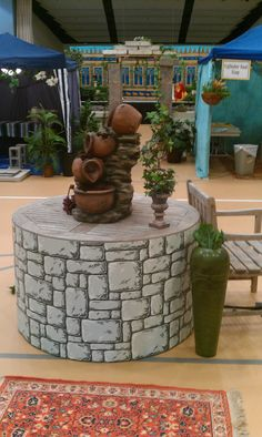 """We anchor our Marketplace with a small electrified fountain.  It sits on a 4' diameter wooden table and we """"skirt"""" it with corrugated cordboard stones.  It is a wonderful place for our older villagers to sit and visit with our tribes."""