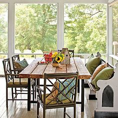 Handcrafted Pine Farm Table | To create an authentic feel, the homeowner sought out nearby artisans to construct the screened porch. The farm table was handcrafted from antique heart pine. | SouthernLiving.com