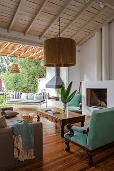 Living de una casa con piso, techo y mesa baja de madera, chimenea, sillones individuales en color celeste y salida al jardín.