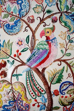 Detail photo of an embroidered piece of fabric with a brightly coloured bird sitting in a tree with paisley-like symbols as the foliage.