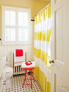 Paint the ceiling a lively shade of yellow for a bold and unexpected treatment. The striped shower curtain in this yellow bathroom repeats the hue and helps carry eyes upward. Pops of cheery cherry in the towels and accent table add a fun touch. Other fixtures are kept neutral to let the yellow shine brightly.