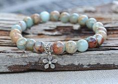 One gorgeous Aqua Terra Jasper gemstone stretch bracelet by Butterfly Warriors Jewelry. A delicate tiny sterling silver daisy charm is added for a touch of whimsy. *Small Sterling Silver 925 Daisy Flo
