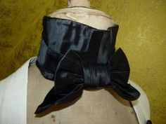 shaped band fastened at the back of the neck with ties, a large metal buckle.velvet and satin - tied into a small gordian knot with short broad ends. worn over the high stand collar of the shirt