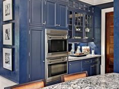 "The classic menswear combination of navy, white and tobacco inspired the palette for this kitchen by architect/homeowner John Laren and interior designer Karen Soojian, ASID. ""Bold contrast is a major design element for the space, as seen in the combination of both white (not shown) and navy cabinets,"" says Soojian. ""This is softened by the introduction of the warm color of the cork floor and the walnut-toned center island."""