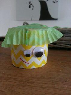 een bekertje van karton vouwen als een doosje, traktatie erin, dichtplakken, hoedje van een cupcakevormpje, oogjes plakken en mondje tekenen.