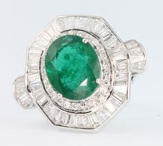 Lot 626, An 18ct white gold emerald and diamond cluster dress ring, the centre stone approx. 9.1ct surrounded by tapered baguettes and brilliant cut diamonds approx. 2.8ct, size O, Est £5000-6000