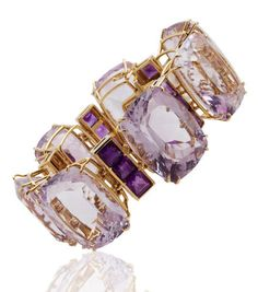 An amethyst bracelet, Tony Duquette designed as seven cushion-shaped light purple amethysts each with square-cut amethyst three-stone spacers; signed Tony Duquette; estimated total light purple amethyst weight: 480.00 carats; estimated total amethyst weight: 37.00 carats; mounted in eighteen karat gold.