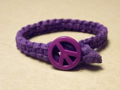 Upcycled purple jersey cotton material braided with a Purple Peace Sign closure. Measures 1/2 wide x 7-1/2 long. Machine washable