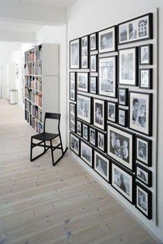 wand met fotolijsten en zwart=wit foto's