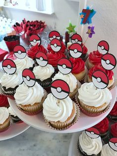 Red and white frosted cupcakes with DIY Poke Ball cupcake toppers as a snack for a Pokémon-themed birthday party. Click or visit FabEveryday.com to see details and DIY instructions for a Pokémon or Pokémon Go themed kid's party, including food, decorations, favors, and party activities.