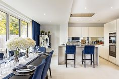 Open plan kitchen in spacious three story home. Blue furniture, blue chairs and blue curtains in contrast with the nude colour palette of the floor and walls, make for a delicate and original set up. Blue Furniture, Blue Curtains, Blue Chairs, Open Plan Kitchen, Colour Schemes, Contrast, Delicate, Palette, Walls