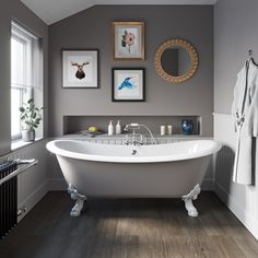 grey toned bathroom with grey freestanding bath and small gallery wall