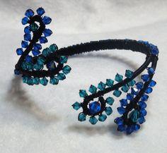 We handmade this wire cuff with anodized aluminum wire then wrapped Swarovski bicones around the swirls!