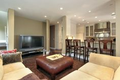 Casual basement family room lounge with sectional suede sofa, brown leather ottoman, mini-bar and large screen television