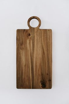 Melda Cutting Board by Nadine Stay. Acacia wood oversized cutting board, charcuterie tray, and bread board. Round handle with dark grains. Kitchen accessories and decor.