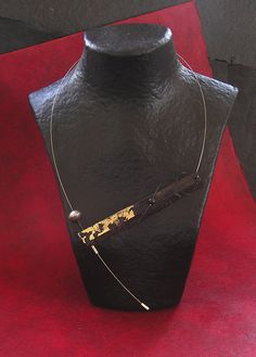 COLLIER CONTEMPORAIN ASYMETRIQUE EN EBENE/ Ebony, gold leaf, African bead, stainless steel wire. — I love the 'styling' on this photograph....