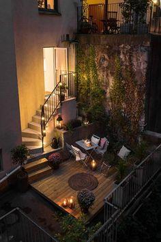 terrazas con encanto, terraza con suelo de tarima, escaleras, mesa y sillas, tapete de mimbre, candelas