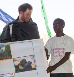 Mutsu hands Harry a canvas of pictures of the children who will benefit from Mamohato Children's Centre while he wears the shawl gifted to him