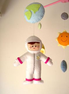 ((( INCLUDES ))) This nursery mobile contains the astronaut, space ship, sun and planets. They are suspended from a pink wood hanger, about 13 x 13.