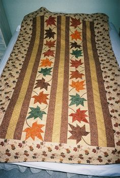 Pancakes with Maple Syrup quilt;  86x51; green, rust, brown, red, orange pieced maple leaves floating between brown and gold strips with maple leaf print border; machined pieced; densely machine quilted with maple leaves and circles; assembled after quilted; rust background; low-loft cotton batting