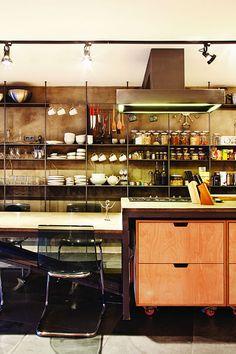 Stěna s úložnými prostory se v kuchyni volně proměňuje v kcuhyňské police.