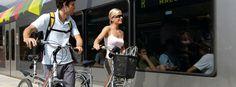 Una coppia cammina con le biciclette a fianco del treno della Val Venosta
