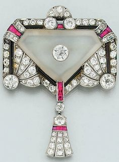 An Art Deco diamond, ruby and onyx brooch. Of stylised Egyptian revival design, the triangular-shaped frosted rock crystal panel with central millegrain-set single old brilliant-cut diamond, within diamond and twin palmette design border with calibré ruby and onyx surround, suspending a lotus blossom design drop, circa 1925. #ArtDeco #EgyptianRevival #brooch