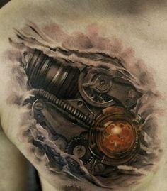 biomechanik-tattoo-herz-brust-mann-getriebe-farbige-kugel