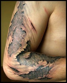 words on a page under torn skin  tattoo-ed on right arm