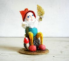 Charming + vintage Christmas spun cotton elf perched on a pine cone and holding a tiny bottle brush tree. He measures approximately 3 tall. Bottom