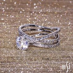 An effortless engagement ring with a double row of 18K white gold pavé-set diamond strands nestled under a single crossover diamond band. This inseparable coil of movement showcases the solitaire setting on a highly polished spiral canvas.