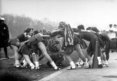 Hempstead High School cheerleaders chanting a cheer as they encircle the school's tiger mascot during game with Uniondale High, 1958.