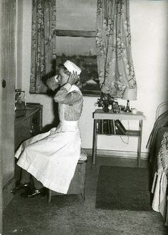 A 1940s nurse adjusts her hat in the mirror before embarking on another day of caring for those in need.