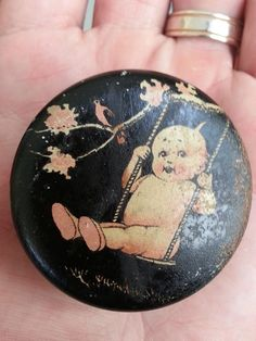 Dating from 1910 to 1920s, here is a wonderful Kewpie metal tin sewing container. Just 2 inches in diameter, it features an iconic Kewpie, created by Rose O'Neill, swinging from a tree. Very cute, and a rare collectible. :)