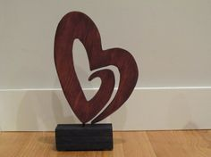 """Hand Cut Wood Heart Sculpture made of Select Pine and Poplar Base. This Red Mahogany Heart stands a total of 15"""" tall on the base. Base is 2 1/4 """" X 6"""" and hand stained with 2 coats premium Black stain. Center dowel holds the Heart Floating above the Base. Heart is 9"""" X 12"""" and is hand stained with a Red Mahogany wood stain. We put felt feet on the bottom so not to scratch where you place it year round.    This sale is for the heart shown in the picture. If you wish for specific colors…"""