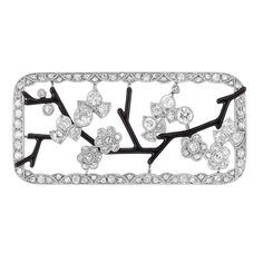 Art Deco Platinum, Diamond and Black Enamel Brooch  The rectangular openwork brooch centering diamond-set blossoms set on slender black enamel branches of angular design, edged by single and rose-cut diamonds, circa 1920, approximately 7.4 dwt.