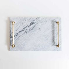 Designed by Katy Skelton, this tray features a sleek marble top and u nfinished brass handles. Dimensions: x x Care: Clean marble with a soft damp sponge. If using brass polish on the handles, make sure to avoid contact with the marble. Marble Tray, Carrara Marble, White Marble, Diy Cutting Board, Elegant Christmas, Cool Bars, My New Room, Granite, Home Accessories