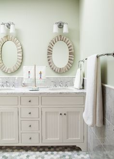 Amazing kids' bathroom features gray marble tiles on lower walls and pale, pale green paint on upper walls framing silver oval scalloped mirrors illuminated by 20light sconces over an ivory dual vanity sink accented with beadboard doors topped with gray marble framing his and her sinks atop gray and green hex tiled floor.