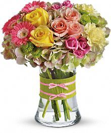 Mini pink gerberas, lush green hydrangea, yellow and pink roses, yellow carnations and green button mums are arranged in a clear concave vase that's trimmed with a chartreuse taffeta ribbon and pink raffia.