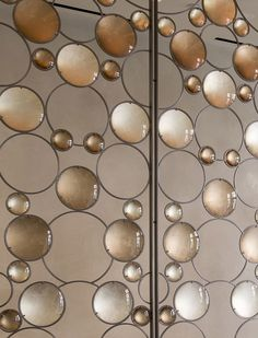Artist Christophe Côme created a 'Bubble Screen', made from iron, industrial crystal and molded glass lenses, that is art and also functions as a room divider in the lobby of a New York building.