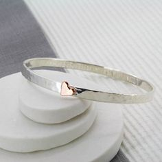 This stunning personalised silver heart bangle features a copper or rose gold heart on the outside, and your personal message on the inside.The bangle can be personalised with up to 50 characters. Available in 3 different sizes. A resizing service is available if you choose the wrong size. Please be aware that there is a charge for this service. The heart is available in rose gold or copper and as this is a handmade item, the size may vary slightly. If you choose the copper heart, it will…